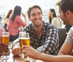 Venner drikker øl udendørs